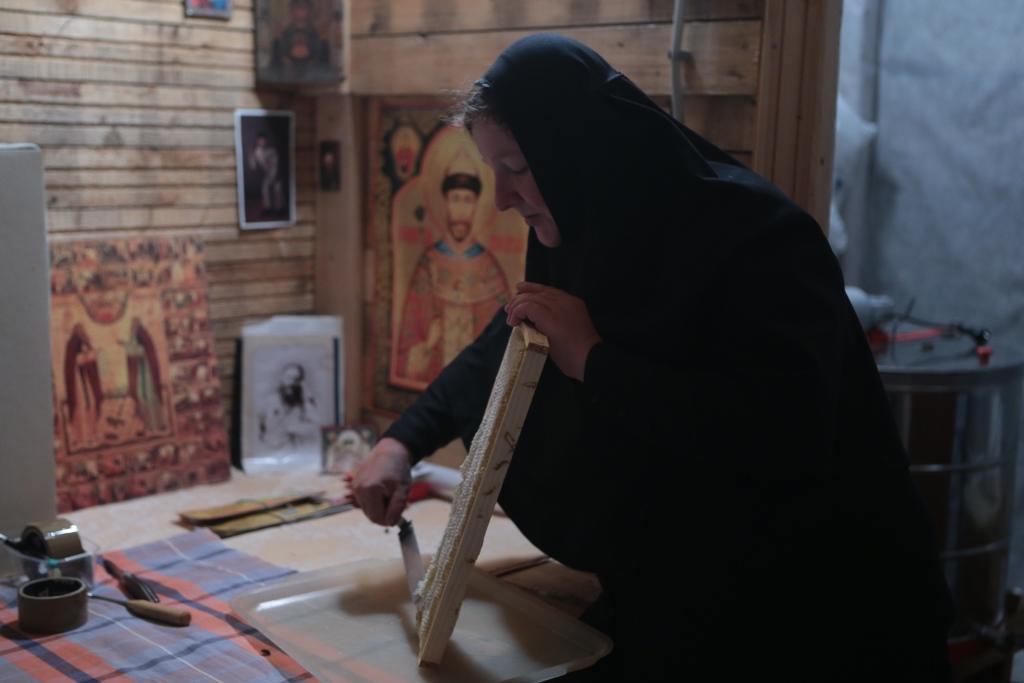 Сестра-пчеловод срезает медовую печатку с сот